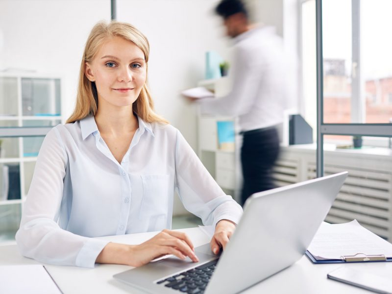 Successful young businesswoman with laptop typing by workplace in office environment